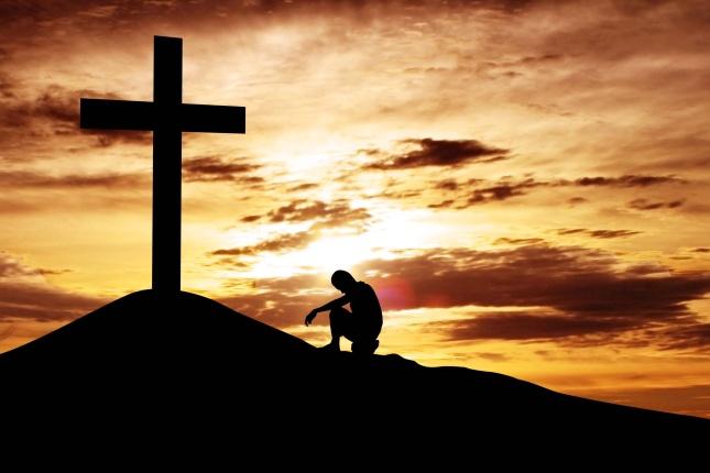 Man sitting desperately under the cross